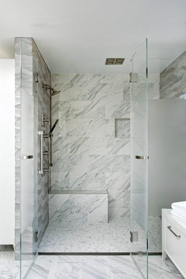 The shower entry boasts a flush, linear drain for easy access.