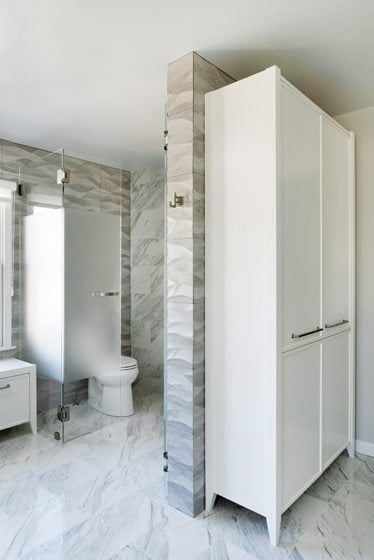 Frosted glass conceals the WC, tucked behind a wing wall that holds a storage cabinet.