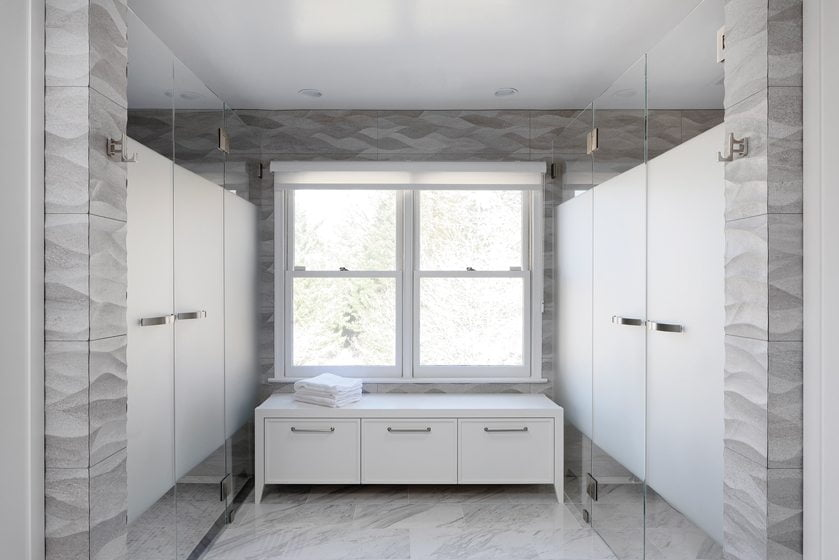 The shower enclosure and WC face each other with a cabinet for towel storage between them.