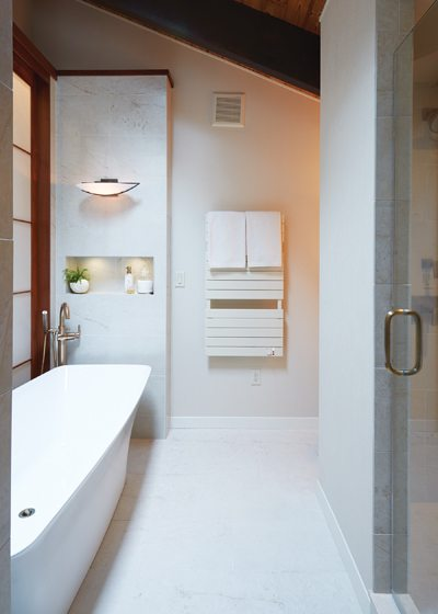 A niche in the wall by the soaking tub holds decorative items and toiletries.