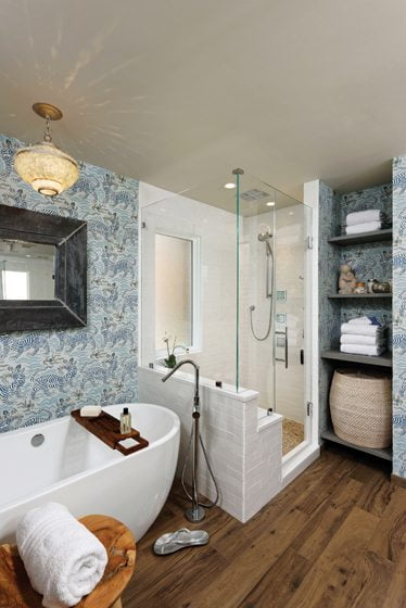 The shower enclosure combines textured white subway tile with a honed-marble floor resembling river rock.
