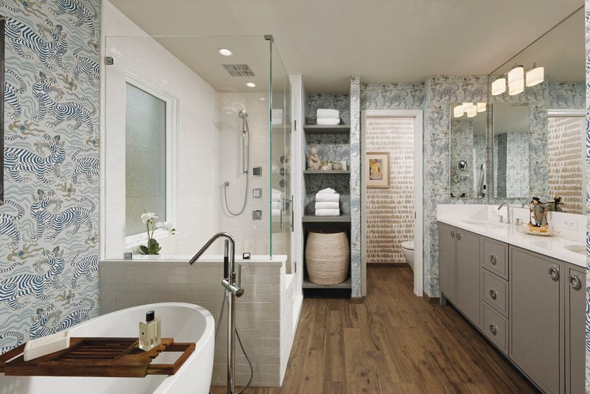 Bold wallpaper patterns are accentuated by crisp, white tile, a gray-painted vanity and a wood-like porcelain floor.