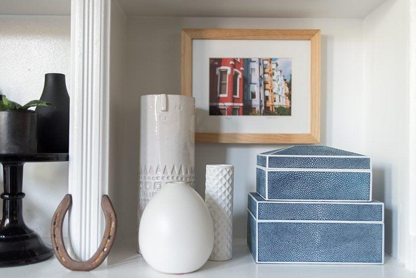 Faux ostrich boxes and ceramics grace a bookshelf.
