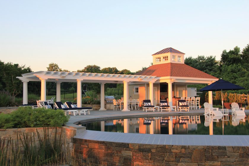 Walnut Hill Landscape Company built a pool house featuring a kitchen area, a flat-screen TV and a separate pergola.