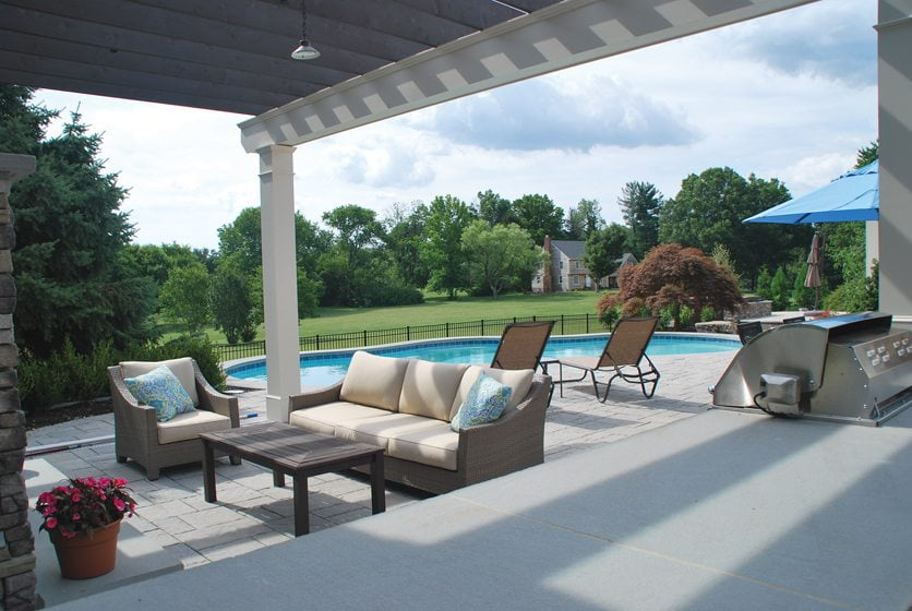 Kane Landscapes designed a poolside pergola that provides shade and anchors a stone fireplace and grilling station.