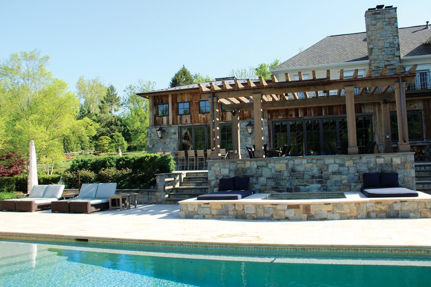 Across the pool, a pergola shades a dining area while a spa below is flanked by custom cushions.