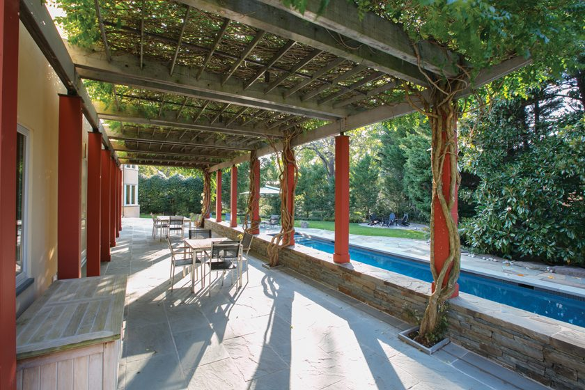 A wisteria-covered pergola encloses the patio overlooking a lap pool and a fire pit beyond.