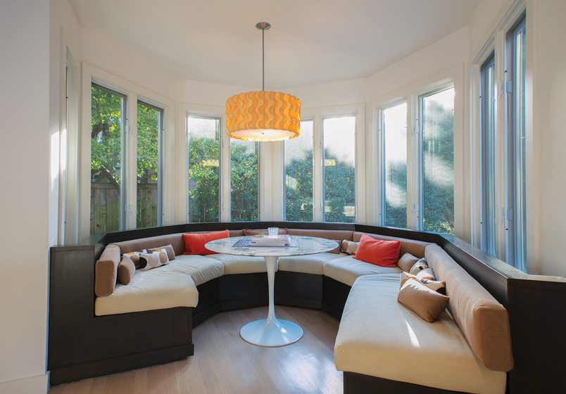 Banquette seating  is built into the existing turret, around a Saarinen Tulip table.