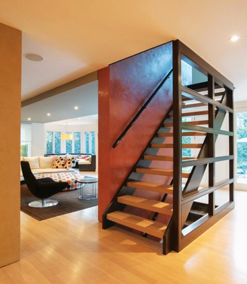 A staircase and floating wall separate the kitchen from the family room beyond.
