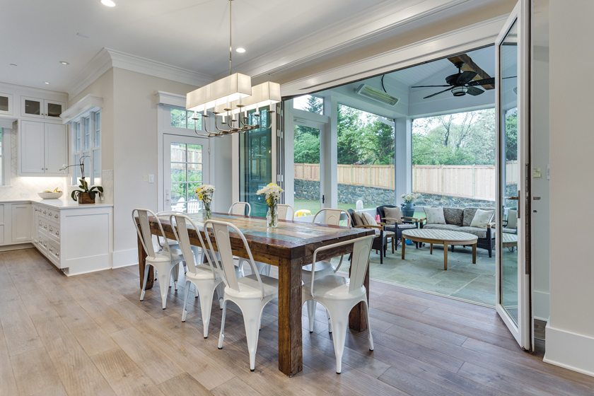 Bi-fold doors open to a back porch in a custom green home by Mid-Atlantic Custom Builders. © HomeVisit