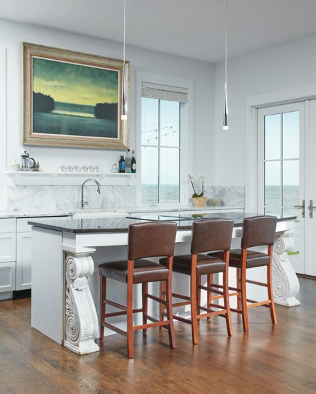 The living space is anchored on one end by the kitchen, enhanced by a Kevin Fitzgerald oil painting.