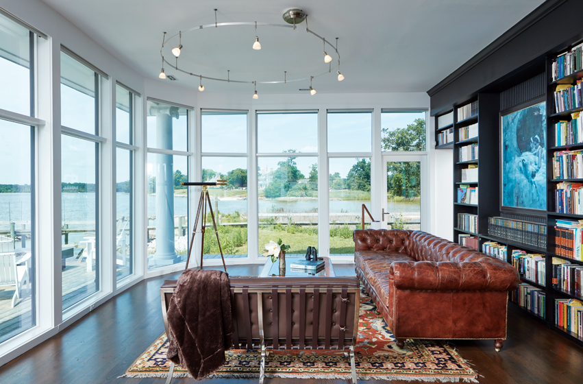 From the living area, a quiet inlet is visible through a curved wall of windows.