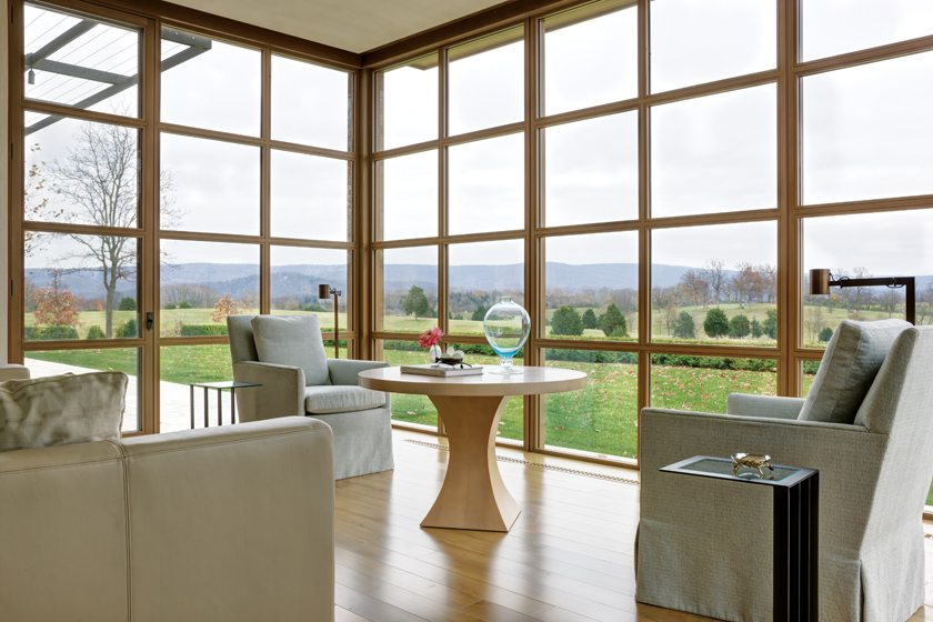 A leather J. Robert Scott sofa and facing Holly Hunt chairs lure guests to relax and reflect on nature.