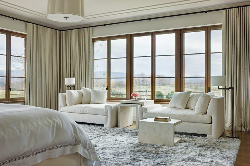 In the master bedroom, window panels in a silky weave by Romo frame panoramic views.