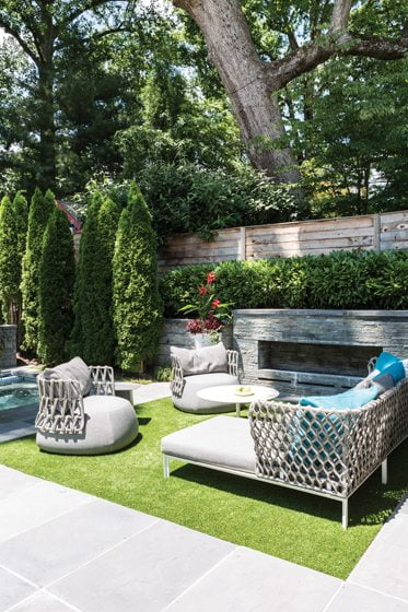 Fine Earth planted a screen of arborvitae for privacy and skip laurel above the al fresco fireplace.