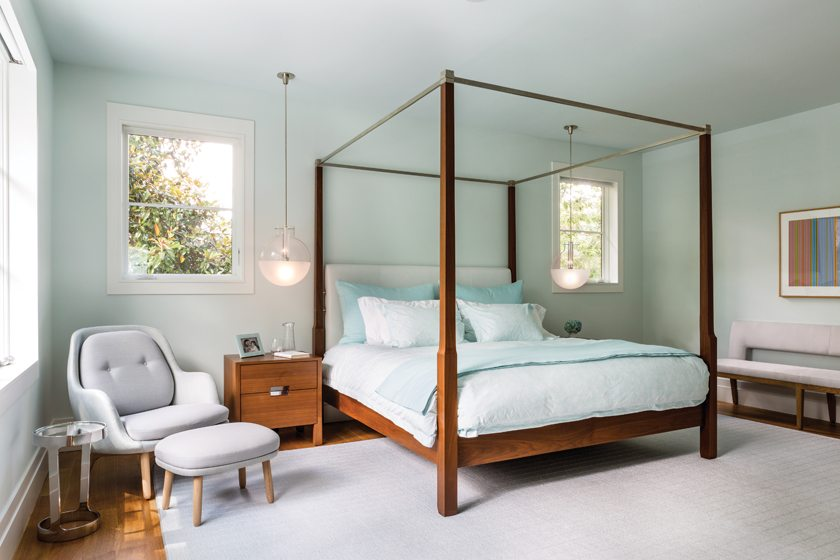 Painted a soft blue, the master bedroom centers on a striking Holly Hunt canopy bed.