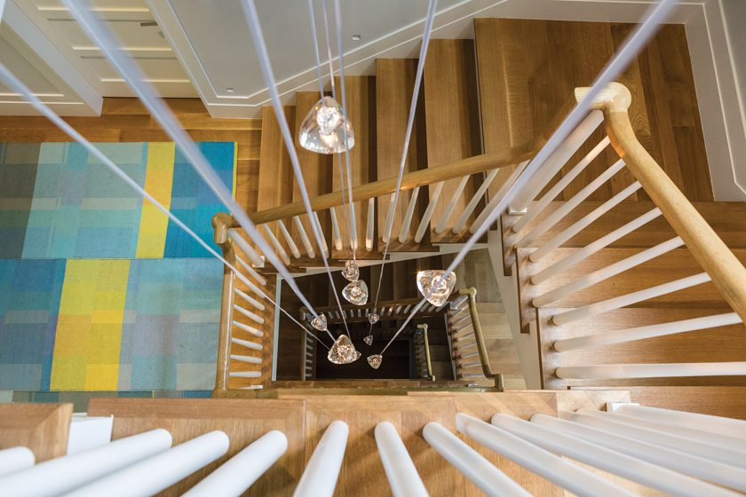 A custom light fixture by Terzani adds a dose of whimsy to the four-story stair.