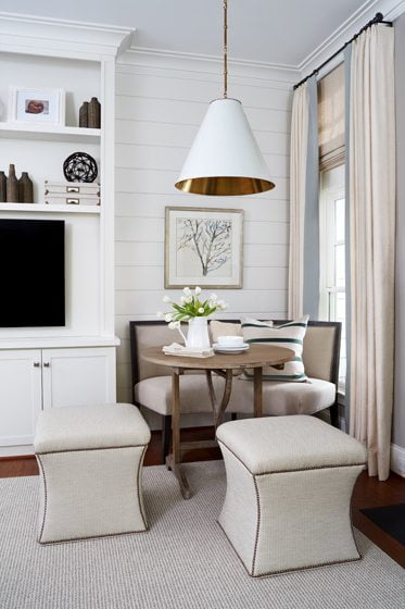A corner nook in the family room is lit by a chic Visual Comfort pendant.