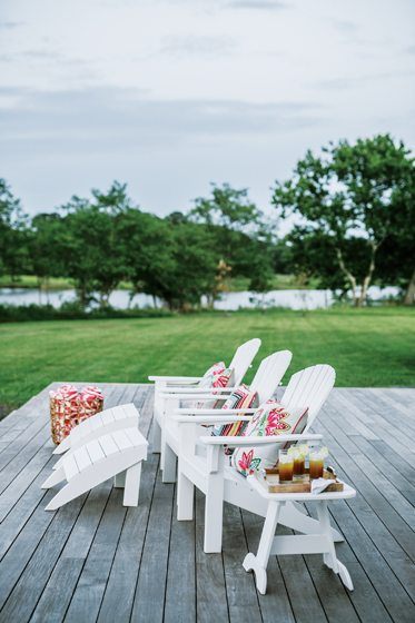 Formerly a screened porch, the deck—complete with Adirondack chairs—is a prime spot for enjoying water views.