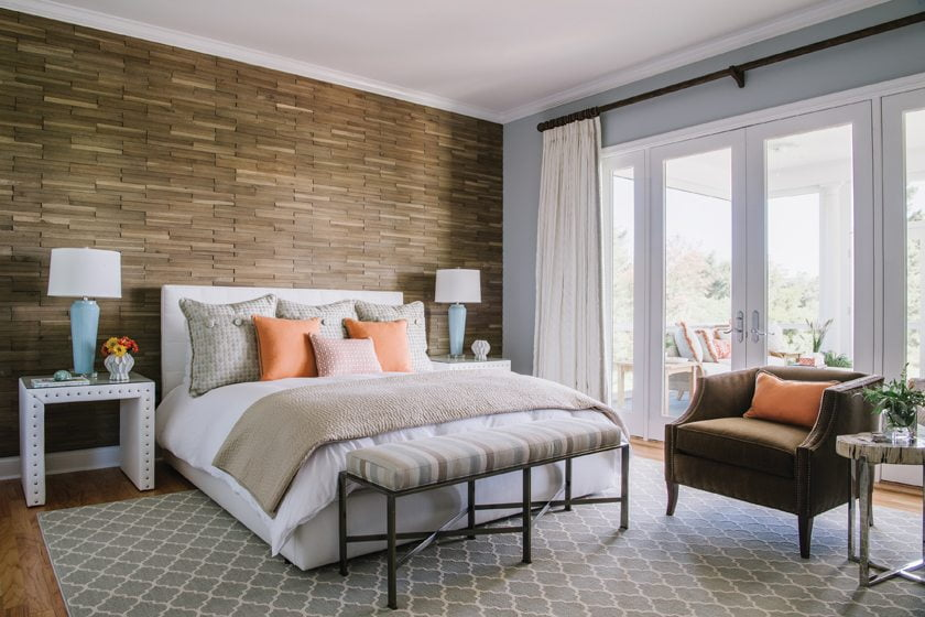A wood accent wall by DuChateau defines the master bedroom; the bench is from Vanguard and the drapery fabric is Kravet.