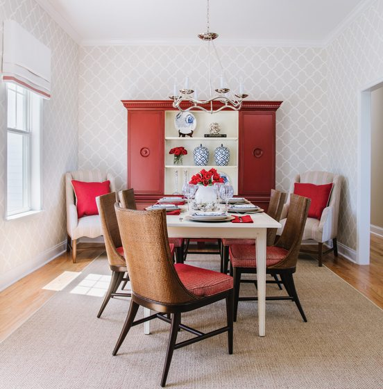 Rattan dining chairs by Palecek pull up to the dining-room table; the chandelier is from Visual Comfort.