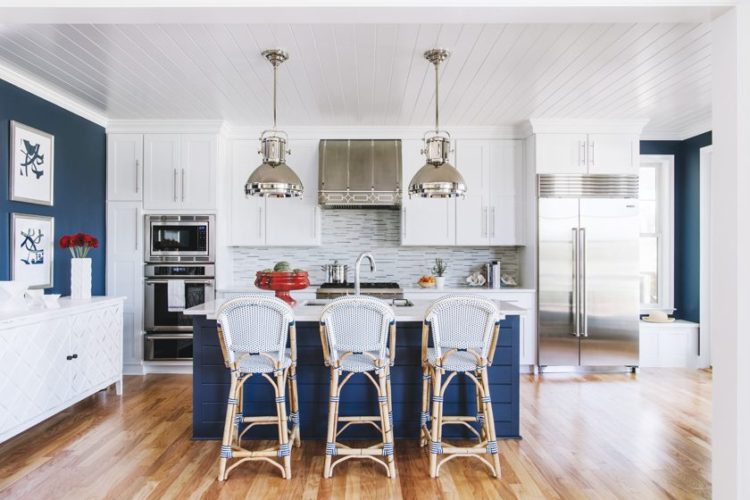 Glass tile by Jeffrey Court creates a reflective backsplash in the airy, open kitchen.