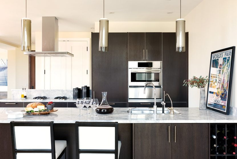 The remodeled kitchen features Poliform cabinetry, quartzite countertops and Elk Lighting pendants.
