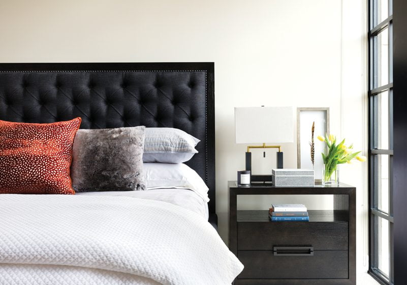The cozy master bedroom holds a bedstead and nightstands from Lexington Home Brands, with bedside lamps by Cyan Designs.