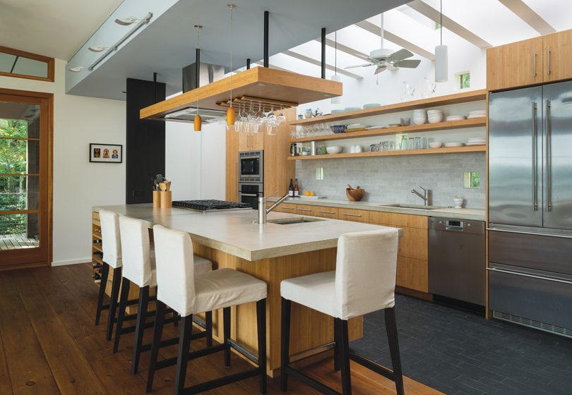 The kitchen marries custom bamboo cabinetry by Potomac Woodwork with a backsplash of porcelain tiles cut in random lengths. The countertops are concrete.