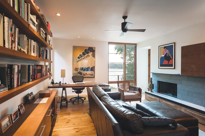 In the library, a fireplace with a Pompeii Scarpaletto basalt surround faces an expanse of cherry millwork. Dynerman designed the desk combining a live-edge walnut slab with a base of ebonized ash.