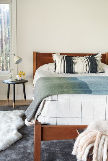 The owners' Shaker-style bedstead in the master bedroom sits atop a Tai Ping carpet.
