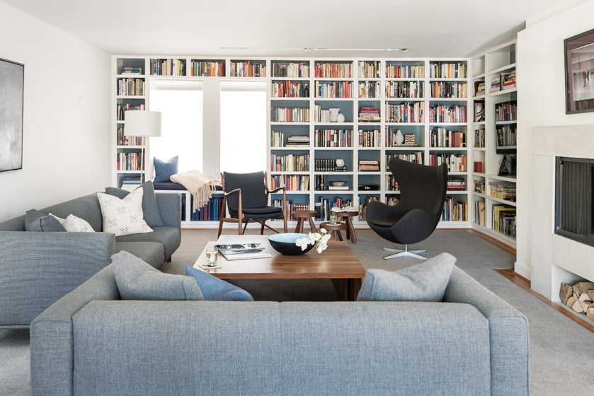 In the living room, DWR sofas, an Arne Jacobsen Egg Chair and a 45 Chair by Finn Juhl  surround a walnut coffee table by Vioski.