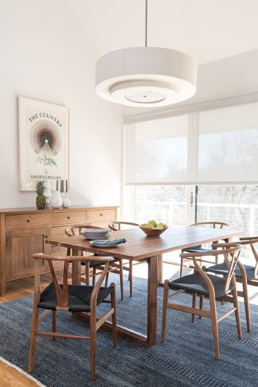 A Fritz Hansen Essay Table and Hans Wegner Wishbone Chairs occupy the dining room.