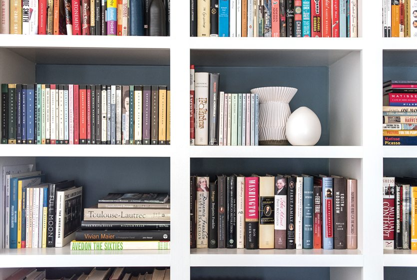 Books share space with white pottery from West Elm.