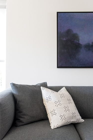 A throw pillow from Salt & Sundry pops against a charcoal-hued sofa.
