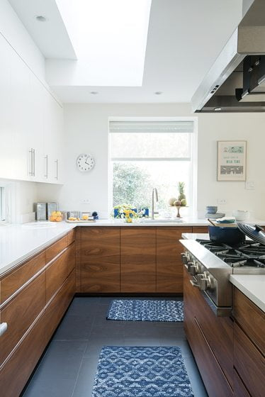 White upper cabinets and Corian countertops in the kitchen temper the dark walnut lower cabinetry.