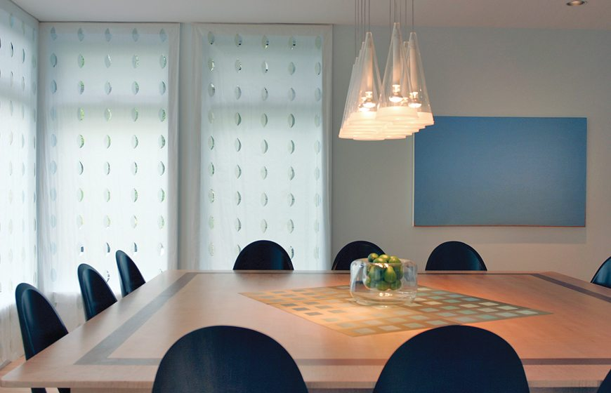 Combining form and function in a McLean dining room, Barbara Hawthorn selected custom-sized window panels by Kinnasand with oval cutouts that admit plenty of light while concealing an unappealing view. The delicate, parchment-like fabric is coated in a wipeable surface, while the leaf-like shapes contain half-moons of fabric tinted pale green and blue. © Kenneth M. Wyner