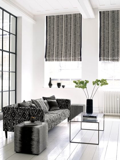 Rockville Interiors, a fabricator of custom window treatments, works in a range of styles and materials. Among them: Roman shades in a bold Clarke & Clarke fabric with banding for strong, graphic contrast. Courtesy of Clarke & Clarke