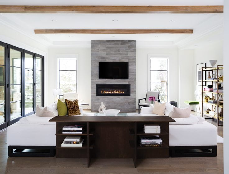 Wooden beams add an organic touch to the living room, where a stone surround frames a linear fire element.