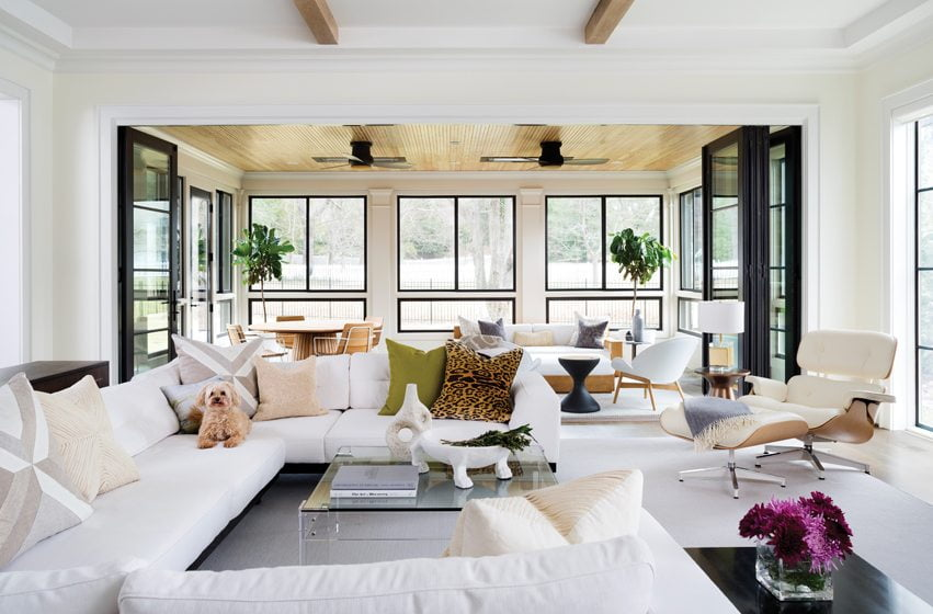 A Restoration Hardware sectional surrounds a glass coffee table from Wisteria in the living room.