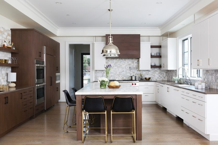 The kitchen combines dark and light cabinets with Caesarstone countertops; the island is topped in marble.