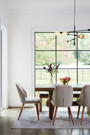 The breakfast nook houses a chandelier, neutral chairs and a table from West Elm.