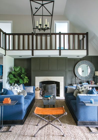 Facing blue sofas by Vanguard flank an orange Noir stool; panels above the fireplace conceal a television.