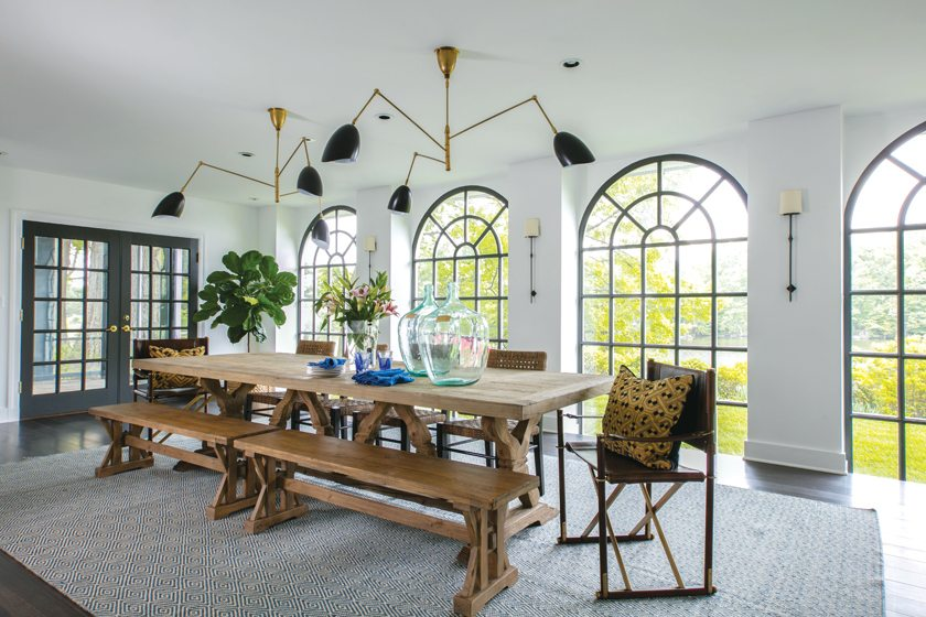 Window mullions painted in Sherwin Williams's Thunder Gray convey a modern aesthetic in the dining room.
