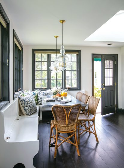 Pitts reinvigorated the home's existing banquette with a marble-topped French bistro table and Hudson Valley pendants.