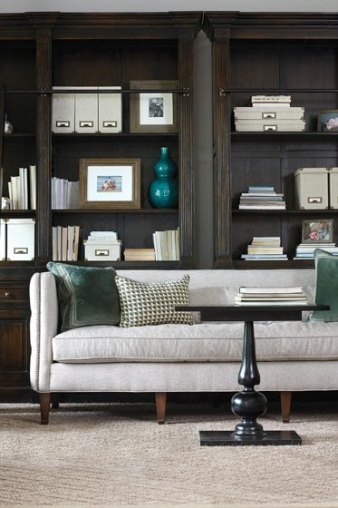 A custom sisal adds natural texture in the reading room, where dark-stained shelves impart the feel of a traditional library.