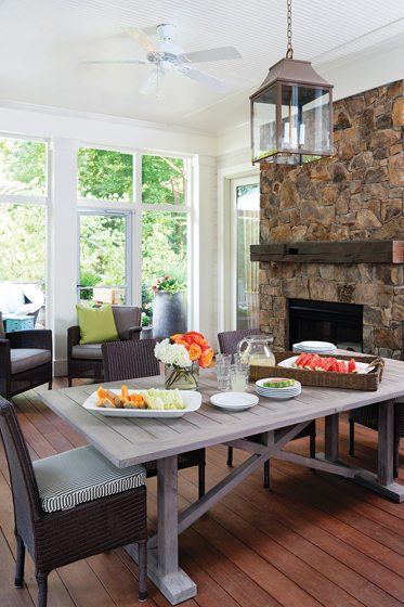 The family room opens to a screened porch with furniture and fabrics from Janus et Cie.