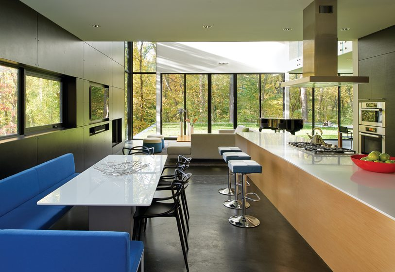 The kitchen accommodates a dining spot featuring an Arco frame bench, a Prismatique table and Kartell chairs.