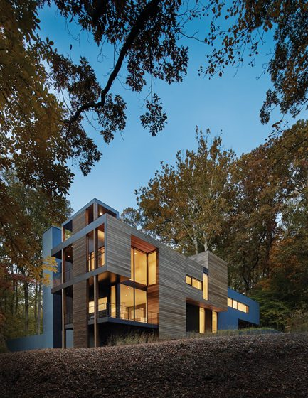 Glass walls throughout the house offer views of the surrounding woods and nearby river.