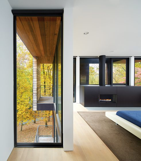 Windows are judiciously placed to capture different perspectives of the architecture and wooded site.
